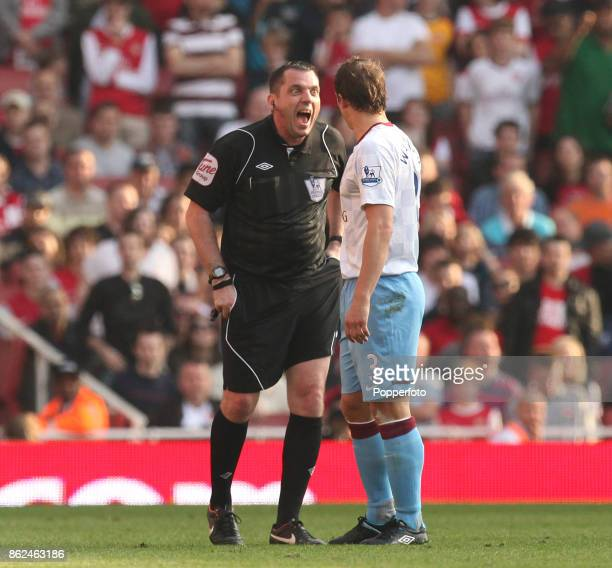 Referee Phil Dowd issues a yellow card to Aston Villa's Stephen Warnock during the Barclays Premier League match between Arsenal and Aston Villa at...