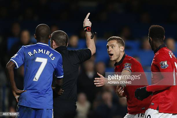 Referee Phil Dowd points offfield as Manchester United's Serbian defender Nemanja Vidic pleads after being shown a straight red card for a challenge...