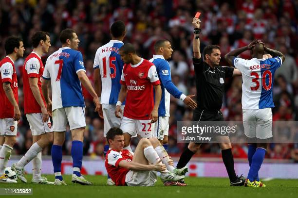Referee Phil Dowd shows a red card to Steven Nzonzi of Blackburn during the Barclays Premier League match between Arsenal and Blackburn Rovers at the...