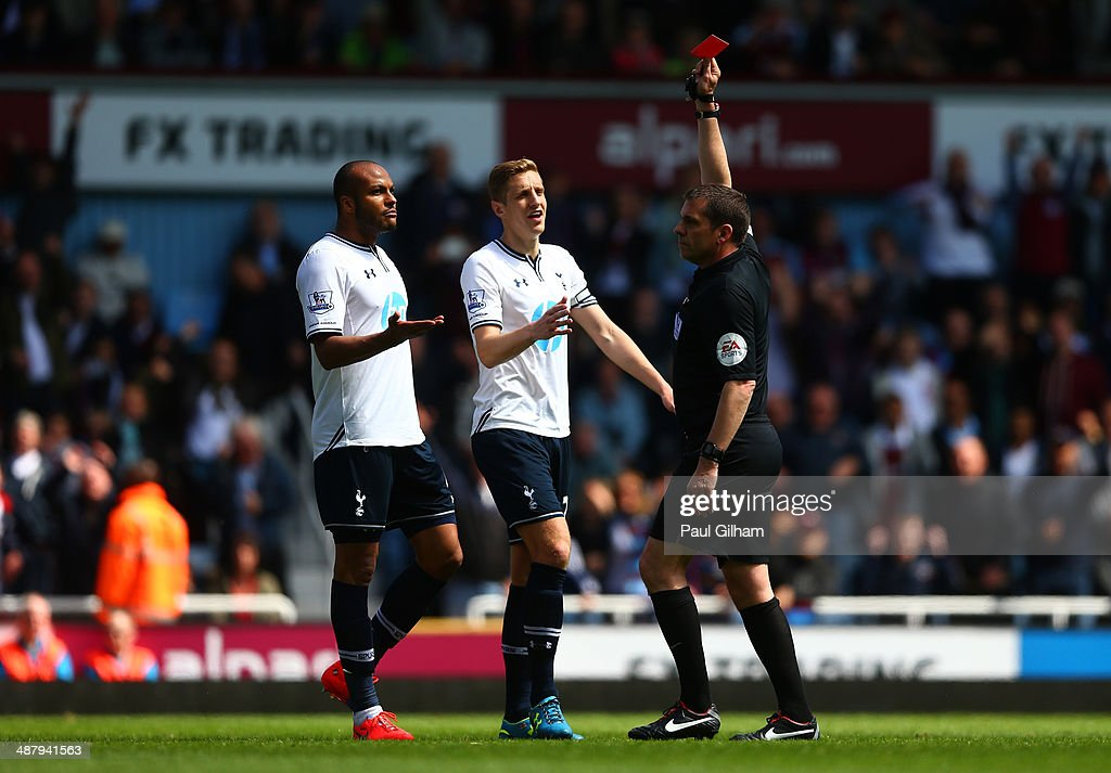 Referee Phil Dowd shows the red card to Younes Kaboul (L) of Spurs as Michael Dawson (C) of Spurs protests during the Barclays Premier League match between West Ham United and Tottenham Hotspur at Boleyn Ground on May 3, 2014 in London, England.