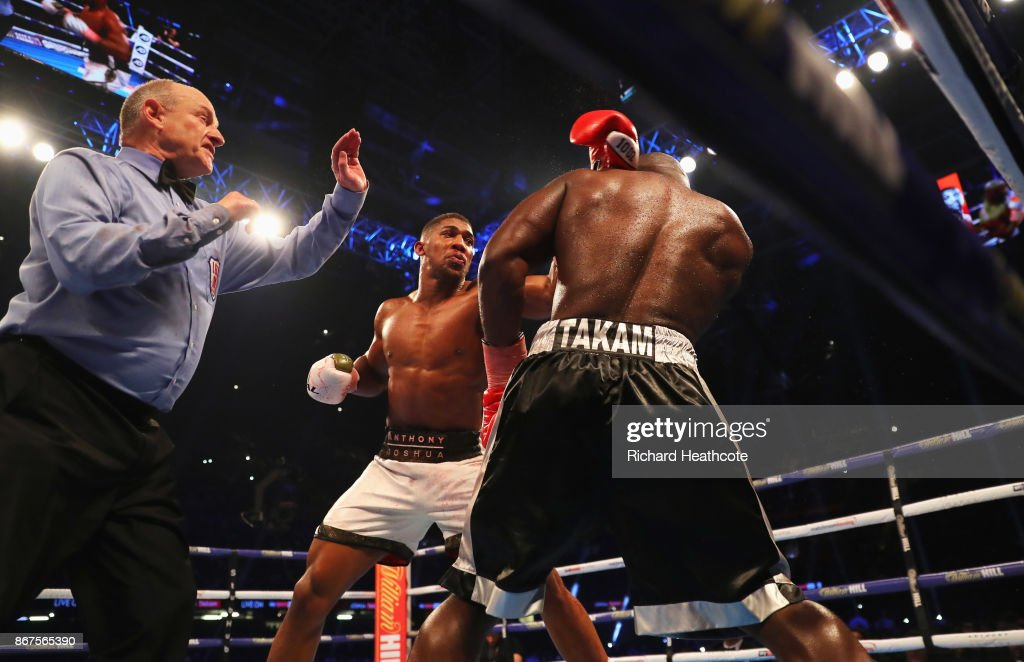 Referee Phil Edwards steps in to stop the fight in the 10th round to hand victory to Anthony Joshua (white trunks) during the IBF, WBA & IBO Heavyweight Championship contest against holds Carlos Takam (black trunks) at Principality Stadium on October 28, 2017 in Cardiff, Wales.