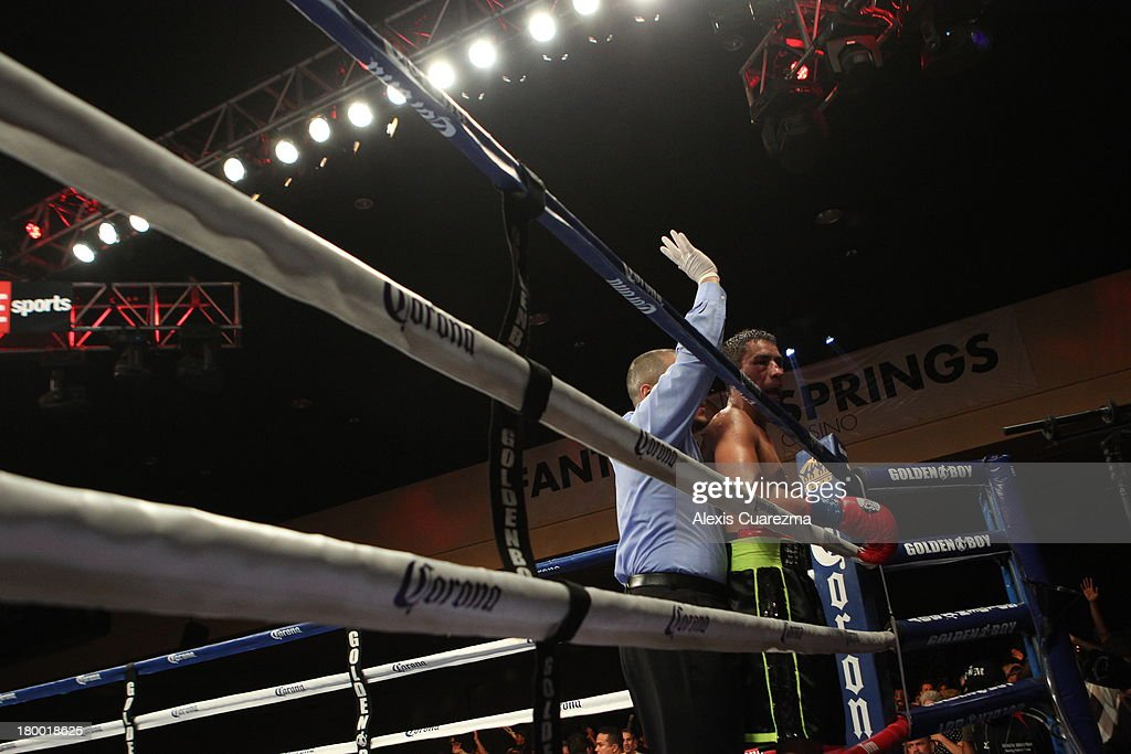 Referee Raul Caiz Jr (L) calls a TKO as he holds Rafael Marquez (R) against the ropes during the 9th round calling a TKO victory for Efrain Esquivias during their fight as the main co-event at the Fantasy Springs Resort Casino - Special Events Center on September 7, 2013 in Indio, California.