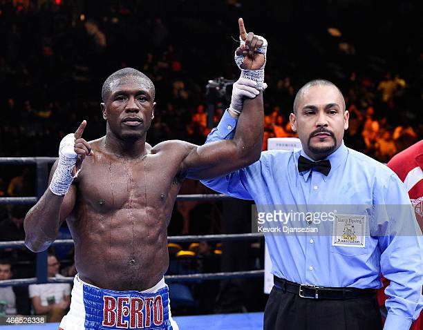Referee Raul Cantu Jr raises the arm of Andre Berto as he celebrates his knock out win over Josesito Lopez during their welterweight bout at Citizens...