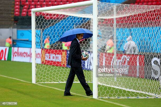 Referee Ravshan Irmatov checks the goal line technology in the bad weather prior to the 2014 FIFA World Cup Brazil Group G match between USA and...