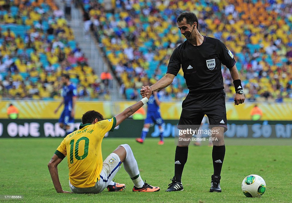 Referee Ravshan Irmatov helps Neymar of Brazil to his feet during the FIFA Confederations Cup Brazil 2013 Group A match between Italy and Brazil at Estadio Octavio Mangabeira (Arena Fonte Nova Salvador) on June 22, 2013 in Salvador, Brazil.