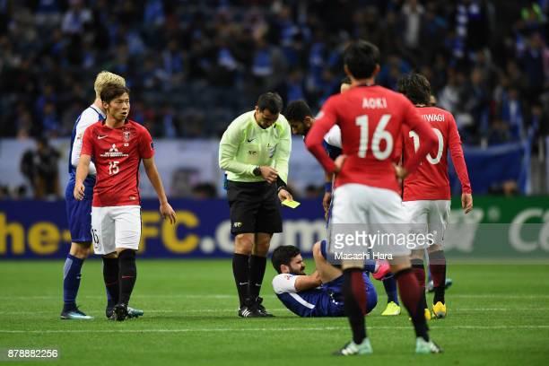 referee Ravshan Irmatov prepares for showing an yellow card to Tomoya Ugajin of Urawa Red Diamonds during the AFC Champions League Final second leg...