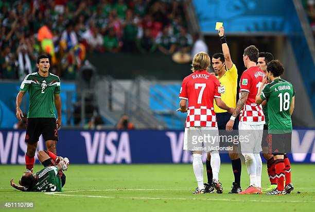 Referee Ravshan Irmatov shows a yellow card to Ivan Rakitic of Croatia during the 2014 FIFA World Cup Brazil Group A match between Croatia and Mexico...