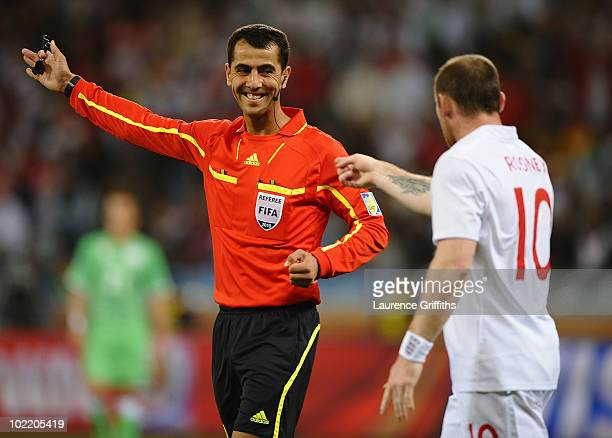 Referee Ravshan Irmatov smiles at Wayne Rooney of England during the 2010 FIFA World Cup South Africa Group C match between England and Algeria at...