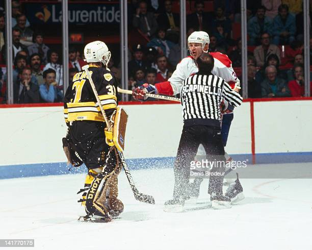 Referee Ray Scapinello holds back Claude Lemieux of the Montreal Canadiens during an argument with Doug Keans of the Boston Bruins Circa 1980 at the...