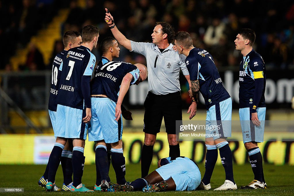 Referee, Reinold Wiedemeijer signals to the bench as he is surrounded by Den Haag players during the Eredivisie match between NAC Breda and ADO Den Haag at the Rat Verlegh Stadium on November 23, 2012 in Breda, Netherlands.