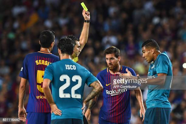 Referee Ricardo De Burgos Bengoetxea shows a yellow card to Real Madrid's Brazilian midfielder Casemiro beside Barcelona's Argentinian forward Lionel...