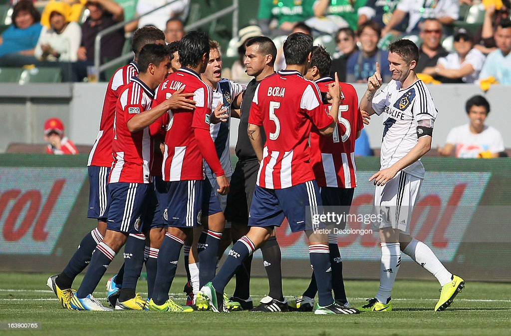 Referee Ricardo Salazar gets between Robbie Keane #7 of the Los Angeles Galaxy and several Chivas USA players after Keane was yellow carded for a foul on Bobby Burling #2 of Chivas USA (not in photo) in the second half of their MLS match at The Home Depot Center on March 17, 2013 in Carson, California. Chivas USA and the Los Angeles Galaxy played to a 1-1 draw.