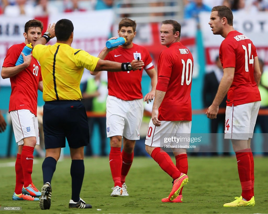Referee Ricardo Salazar (2nd L) speaks to Adam Lallana (L), Steven Gerrard (C), Wayne Rooney (2nd R) and Jordan Henderson (R) as Salazar delays the match due to inclement weather in the first half during the International Friendly match between England and Honduras at Sun Life Stadium on June 7, 2014 in Miami Gardens, Florida.