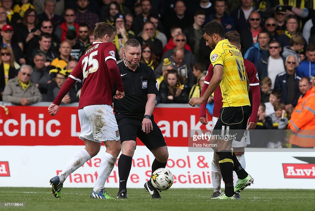 Referee Richard Clark throws in the ball as Joel Byrom of Northampton Town and Kevin Stewart of Burton Albion contest a drop ball during the Sky Bet League Two match between Burton Albion and Northampton Town at Pirelli Stadium on April 25, 2015 in Burton-upon-Trent, England.
