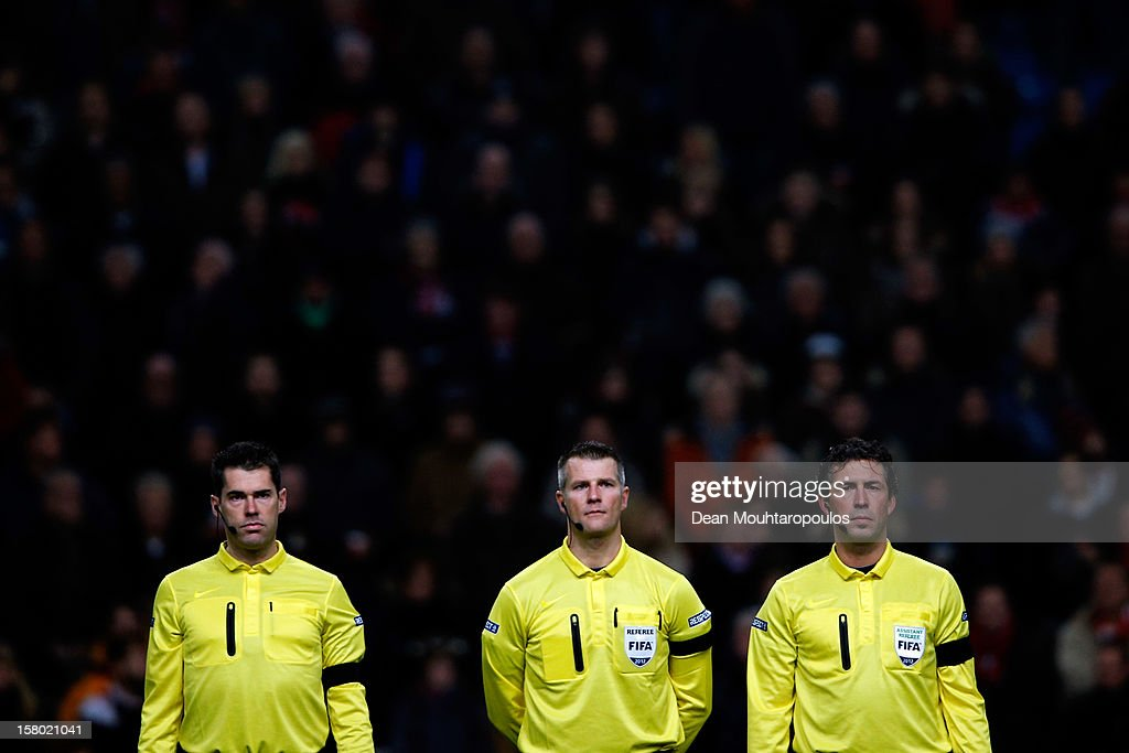 Referee, Richard Liesveld (C) and his officials stand for the minute silence for prior to the Eredivisie match between Ajax Amsterdam and FC Groningen at Amsterdam Arena on December 8, 2012 in Amsterdam, Netherlands. The minute silence was for Richard Nieuwenhuizen, 41, who was attacked while officiating for the Buitenboys team in an under-17 match in Almere last Sunday. He died the following day.