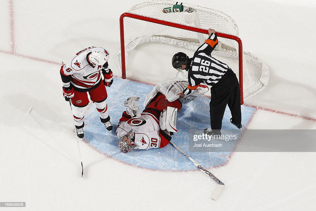 Referee Rob Martell #26 and Tim Gleason #6 check the condition of goaltender Cam Ward #30 of the Carolina Hurricanes after he was injured in second period action against the Florida Panthers at the BB&T Center on March 3, 2013 in Sunrise, Florida. The Hurricanes defeated the Panthers 3-2.