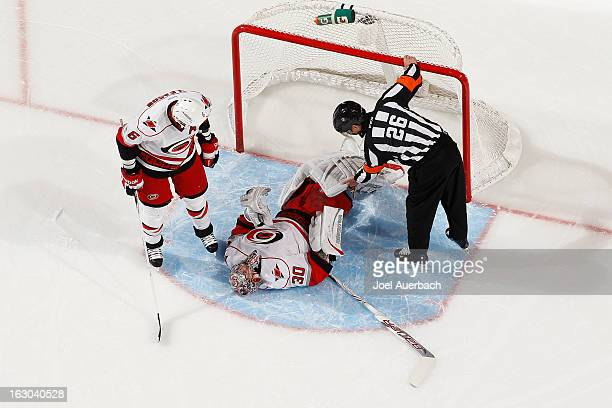 Referee Rob Martell and Tim Gleason check the condition of goaltender Cam Ward of the Carolina Hurricanes after he was injured in second period...