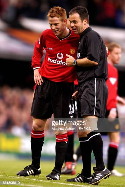 Referee Rob Styles has a word with Manchester United's Michael Stewart