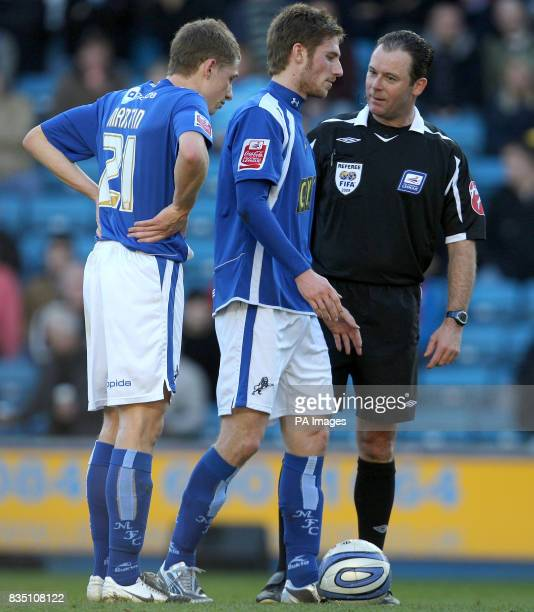 Referee Rob Styles with Millwall's James Henry and David Martin during the CocaCola League One match at The Den London