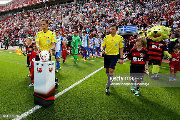 Referee Robert Hartmann picks up the ball prior to the Bundesliga match between Bayer Leverkusen and 1899 Hoffenheim at BayArena on August 15 2015 in...
