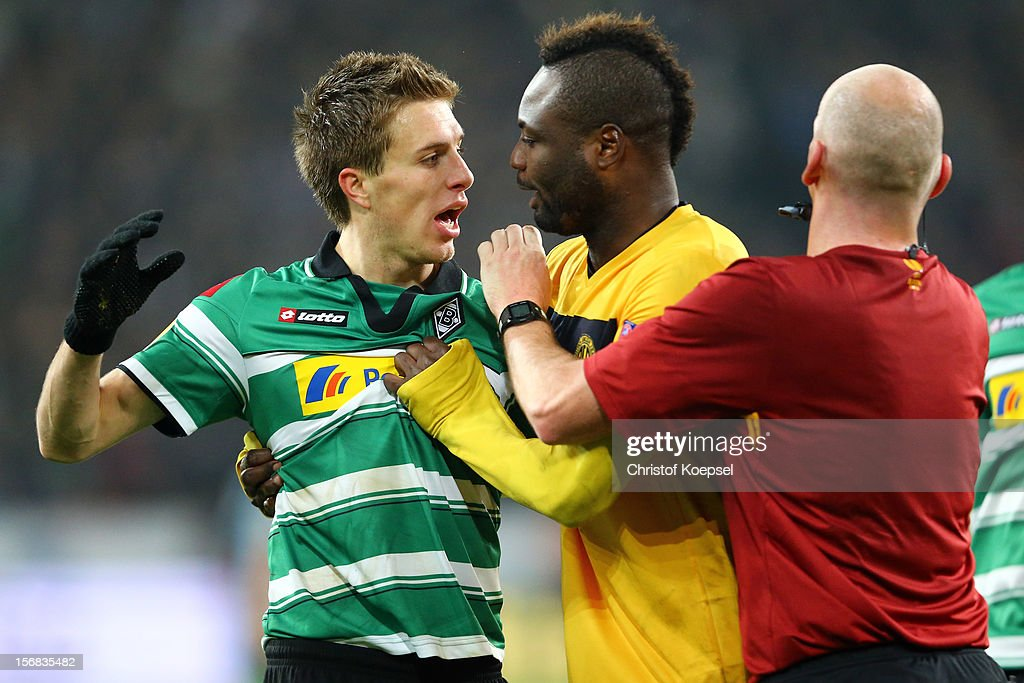 Referee Robert Madden of Scotland (R) stops Patrick Herrmann of Moenchengladbach (L) and Paulo Sergio of Limassol (C) struggling during the UEFA Europa League group C match between Borussia Moenchengladbach and AEL Limassol FC at Borussia Park Stadium on November 22, 2012 in Moenchengladbach, Germany.