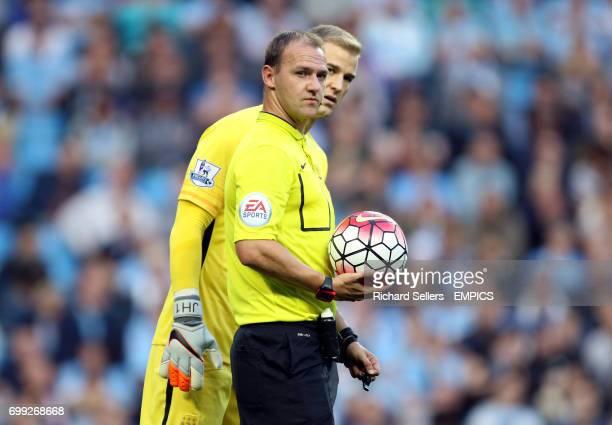 Referee Robert Madley and Manchester City goalkeeper Joe Hart