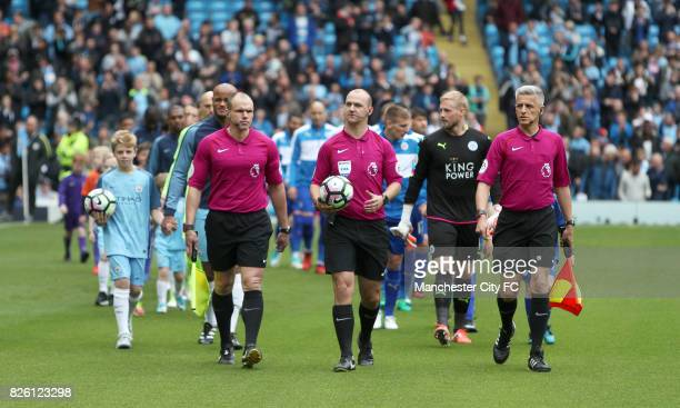 Referee Robert Madley and officials head out onto the pitch