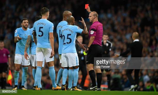 Referee Robert Madley issues a red card to Manchester City player Kyle Walker during the Premier League match between Manchester City and Everton at...