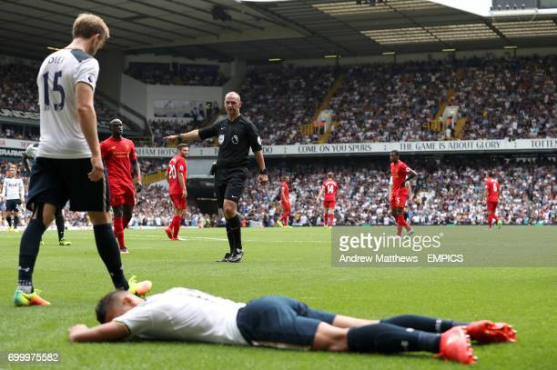 Referee Robert Madley points to the penalty spot after a fall from Tottenham Hotspur's Erik Lamela on Liverpool's Roberto Firmino