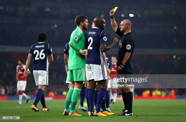 Referee Robert Madley shows a yellow card to Allan Nyom of West Bromwich Albion as he concedes a penaltyduring the Premier League match between...