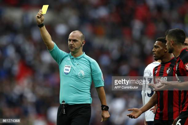 Referee Robert Madley shows a yellow card to Bournemouth's BosnianHerzegovinian goalkeeper Asmir Begovic during the English Premier League football...