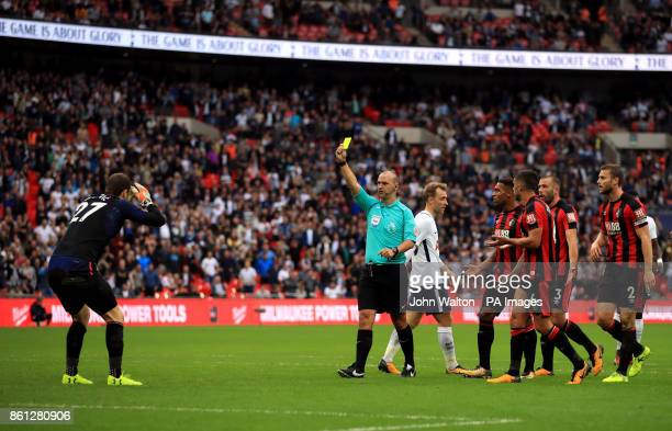 Referee Robert Madley shows AFC Bournemouth goalkeeper Asmir Begovic a yellow card during the Premier League match at Wembley Stadium London
