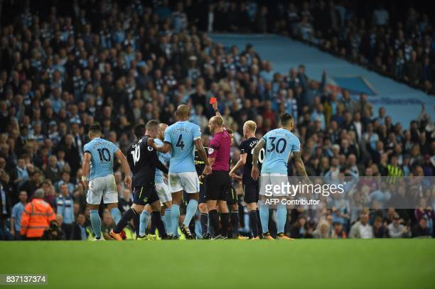 Referee Robert Madley shows the red card to Everton's French midfielder Morgan Schneiderlin during the English Premier League football match between...