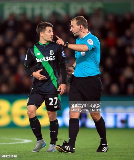 Referee Robert Madley speaks with Stoke City's Bojan Krkic