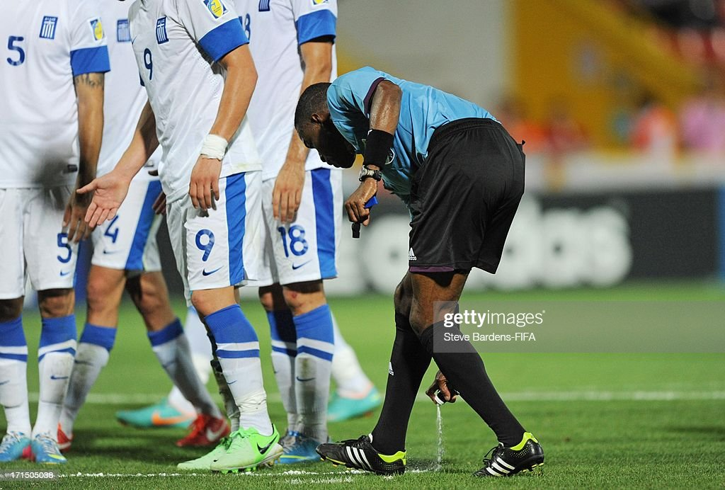 Referee Roberto Moreno of Panama sprays a foam marker line onto the pitch to illustrate where a Greek defensive wall must stand during the FIFA U20 World Cup Group D match between Mali and Greece at Kamil Ocak Stadium on June 25, 2013 in Gaziantep, Turkey.