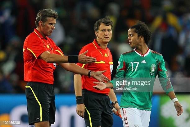 Referee Roberto Rosetti asks Giovani Dos Santos of Mexico to leave after an appeal to referee assistant Stefano Ayroldi over the Carlos Tevez goal...