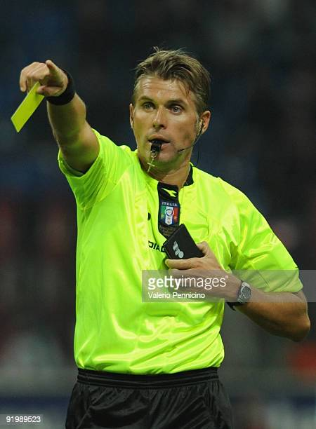 Referee Roberto Rosetti assigns a yellow card during the Serie A match between AC Milan and AS Roma at Stadio Giuseppe Meazza on October 18 2009 in...