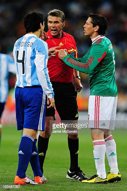Referee Roberto Rosetti intervenes as Nicolas Burdisso of Argentina and Guillermo Franco of Mexico argue during the 2010 FIFA World Cup South Africa...
