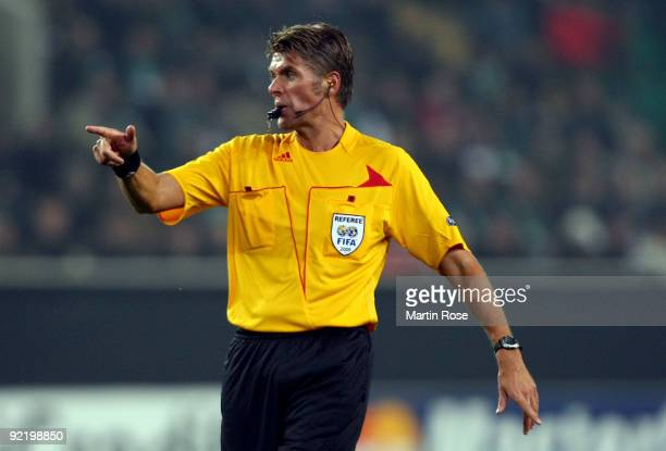 Referee Roberto Rosetti makes a point during the UEFA Champions League Group B first leg match between VfL Wolfsburg and Besiktas at the Volkswagen...