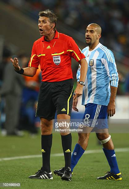 Referee Roberto Rosetti officiates as Juan Veron of Argentina looks on during the 2010 FIFA World Cup South Africa Round of Sixteen match between...