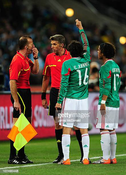 Referee Roberto Rosetti speaks to referee assistant Stefano Ayroldi over the Carlos Tevez goal during the 2010 FIFA World Cup South Africa Round of...