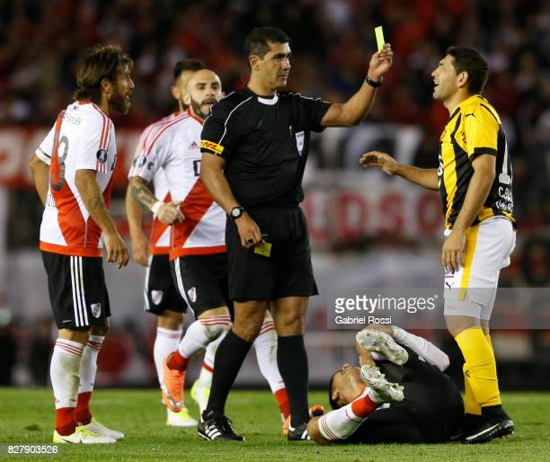 Referee Roddy Zambrano shows a yellow card to Luis Alberto Cabral of Guarani during a second leg match between River Plate and Guarani as part of...