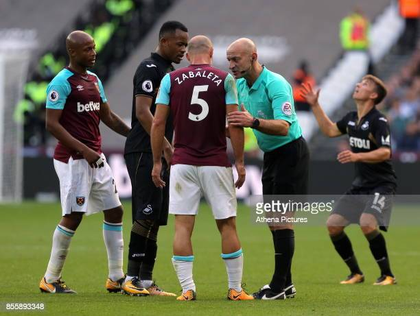 Referee Roger East has a word with Jordan Ayew of Swansea City after a foul by Pablo Zabaleta of West Ham during the Premier League match between...