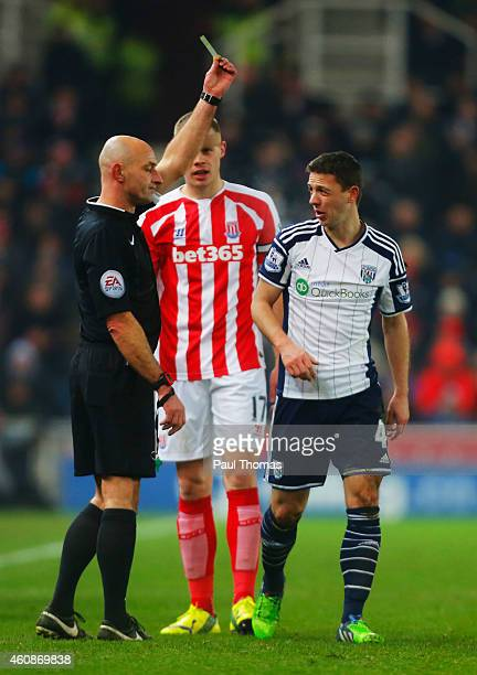 Referee Roger East shows a yellow card to Chris Baird of West Bromwich Albion during the Barclays Premier League match between Stoke City and West...