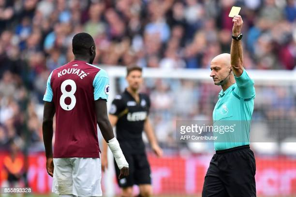 Referee Roger East shows a yellow card to West Ham United's Senegalese midfielder Cheikhou Kouyate during the English Premier League football match...