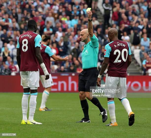 Referee Roger East shows Cheikhou Kouyate of West Ham a yellow card during the Premier League match between West Ham United and Swansea City at the...
