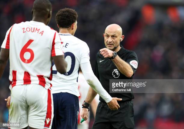 Referee Roger East talks to Dele Alli of Tottenham Hotspur and Kurt Zouma of Stoke City during the Premier League match between Tottenham Hotspur and...
