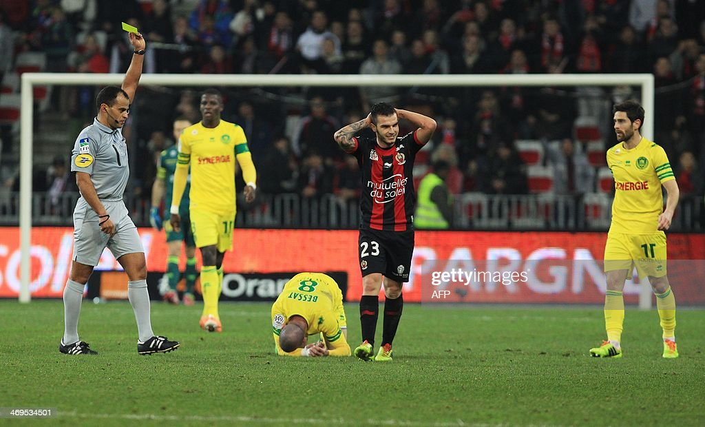 Referee Said Ennjimi (L) gives a yellow card to Nice's French forward Alexy Bosetti (Center R) during the French L1 football match between OGC Nice (OGCN) and FC Nantes (FCN) on February 15, 2014, at the Allianz Riviera stadium, in Nice, southeastern France.