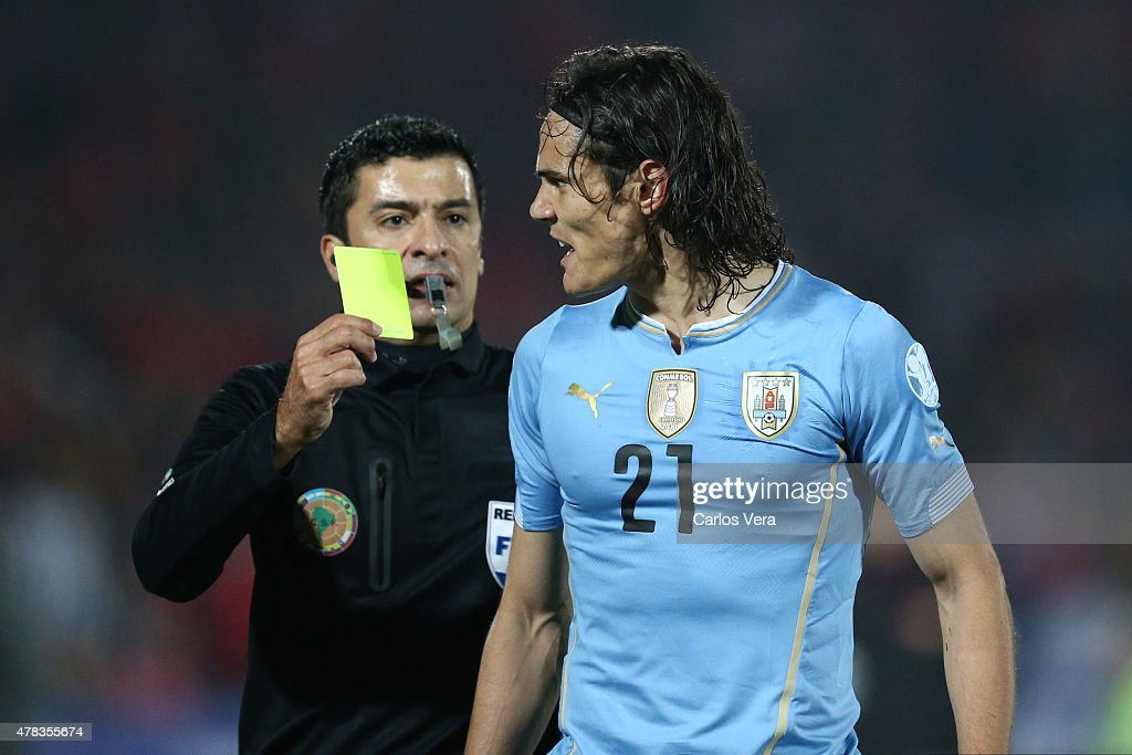 Referee <a gi-track='captionPersonalityLinkClicked' href=/galleries/search?phrase=Sandro+Ricci&family=editorial&specificpeople=9145717 ng-click='$event.stopPropagation()'>Sandro Ricci</a> shows a yellow card to <a gi-track='captionPersonalityLinkClicked' href=/galleries/search?phrase=Edinson+Cavani&family=editorial&specificpeople=4104253 ng-click='$event.stopPropagation()'>Edinson Cavani</a> of Uruguay during the 2015 Copa America Chile quarter final match between Chile and Uruguay at Nacional Stadium on June 24, 2015 in Santiago, Chile.