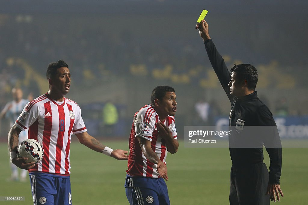Referee <a gi-track='captionPersonalityLinkClicked' href=/galleries/search?phrase=Sandro+Ricci&family=editorial&specificpeople=9145717 ng-click='$event.stopPropagation()'>Sandro Ricci</a> shows a yellow card to Richard Ortiz of Paraguay during the 2015 Copa America Chile Semi Final match between Argentina and Paraguay at Ester Roa Rebolledo Stadium on June 30, 2015 in Concepcion, Chile.